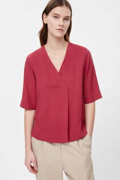 Designed to drape on the body, this top has wide half sleeves and a deep, crossover v-neckline. With a folded pleat along the front, it is made from lightly textured fabric that has loose, fluid quality. Blouse Styles, Blouse Designs, Cos Fashion, Fashion Hacks, Fashion Ideas, Batik Blazer, Simple Pakistani Dresses, Kurta Patterns, Crop Top Dress
