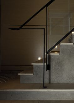 Coventry Street Staircase. Timber walls, limestone and concrete floors and black steel handrail