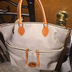 """Dooney & Bourke Gray Tote Brand new without tags. Very durable, easy to clean, lightweight!!  H 12"""" x W 6"""" x L 12"""" Inside zip pocket. Two inside pockets. Two outside zip pockets. Cell phone pocket. Inside key hook. Zipper closure. Detachable strap with shoulder pad. Handle drop length 6"""". Strap drop length 22"""". Lined. Feet. Dooney & Bourke Bags Totes"""