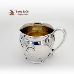 "American sterling silver child's cup featuring applied images of a young girl in a rain hat accented by foliate decorations with a foliate form handle. The interior of the cup is gilt. Made by Gorham 1907. Inscribed ""Good Morning June 11th 1907 Uncle James"" in ornate period script on the bottom of the cup."