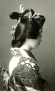 A Geiko (Geisha) dressed in the Genroku style, with her hair in the Shimada-mage hairstyle of the Middle Edo period (1688-1715). It is believed that the yujo (ladies of pleasure) of Shimada created the hairstyle. 1920s
