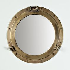"Nautical Brass Porthole Mirror nsert vintage nautical style with this porthole mirror in beautiful antiqued brass. A classic coastal icon to brighten a bath or create a window to the world accent in any room. (20.25""Wx1""D) Diameter of inner mirror (14.5"") Product SKU: MW10026 BZ Price: $229.00"