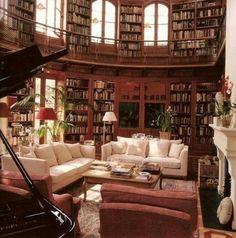 La bibliotecha en la casa tiene muchos libros y un sofa.