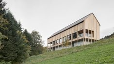 This timber-clad residence by Bernardo Bader Architects appears to be raised on stilts above chunky concrete foundations in Austrian mountains