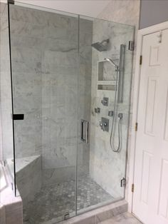Marble shower with hexagon floor and frameless shower door