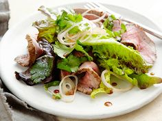 Grilled Thai Beef Salad: 1 lb flank steak, about 1-1.5-in. thick 3 tbs lime juice, divided 3 tbs soy sauce 3 tbs canola oil 2 tbs brown sugar 1 tsp minced garlic 1.5 tsp minced ginger 1.25 tsp red curry paste or chili-garlic sauce 1/2 head red-leaf lettuce, torn (~6 c.) 3 shallots, thinly sliced (~1/2 c.), divided, for garnish 1/2 c. cilantro leaves, rinsed & dried 1 c. basil leaves, sliced into ribbons
