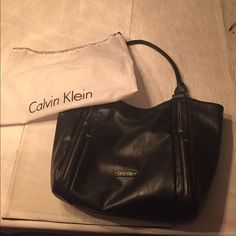 """Calvin Klein large reversible tote Calvin Klein reversible tote, black exterior with silver tone hardware. 4-side zipper compartments. 2 leather handles with 12"""" drop. Gray leather interior. Used for just a short time, in excellent condition with minor wear.                        Measures approximately 18"""" wide, 13""""high, and 5.5"""" depth. Comes with dust bag. Calvin Klein Bags Totes"""