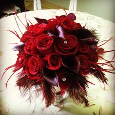 2 dozen black magic roses and 8 stems of plum mini calla lilies.  The flowers are surrounded by dark red feathers, and the stems are all wrapped in ivory satin ribbon.