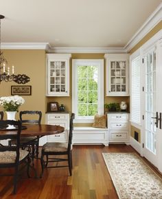 Rich gold walls are complimented with white cabinets and warm woods.