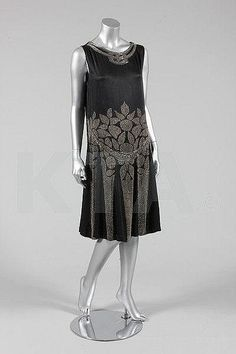 A black satin flapper dress, circa 1927, adorned with gold and silver seed and bugle beads, Kerry Taylor Auctions