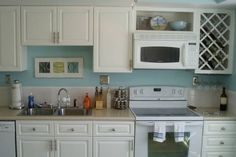 Really like the turqoise walls and white cabinets together.