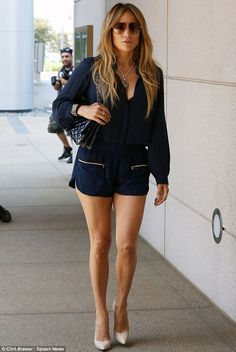 Summer chic: The star sported a plunging navy blouse with tiny zippered shorts and off-white pumps