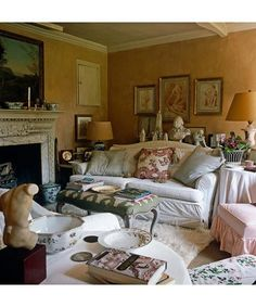 Nicky Haslam ~ sofa in the sitting room  covered with Jaisalmer by John Stefanidis, a flokati rug, busts, engravings, tan lampshades that cast flattering golden light, and old china for ashtrays.