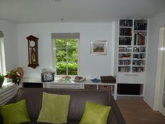 de vensterbankkast rondom loopt uit in een hoge boekenkast