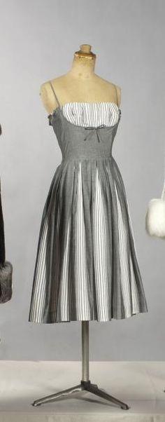 Jacques Esterel, c.1959 Robe à fines bretelles, bustier balconnet à effet de rayures soulignées d'un noeud et de plis s'ouvrant à partir de la taille faisant un trompe l'oeil par le coton gris et les rayures. Griffe blanche, graphisme noir