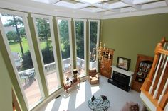 Gorgeous floor-to-ceiling windows in fireside family room with neutral green color painted on walls.  915-Golf-View-Court-Dacula-GA-30019