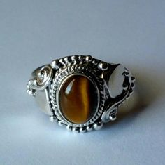 Unique tiger eye sterling silver ring! Beautiful scrollwork on this one!  Rich color to the stone. Clearing out my massive jewelry collection to help furnish my half-empty house!  I've never even worn this one except to model here, as it's a bit too small for me.  I envy the girl this fits!!!    Shinier in person than the pics show.  Marked 925. handcrafted Jewelry Rings