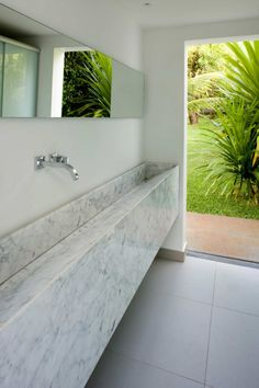 Bathroom by Atria Arquitetos, Brasília, Brazil.  White Carrara Hand-Carved Sink  www.westsidetile.com