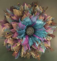 Stunning large peacock wreath by A Noble Touch. This is sure to be a conversation piece. The colors of the deco mesh represent the colors in a peacock feather. The black center is adorned with blue and green gems and the flower is adorned with actual peacock feathers throughout it. This
