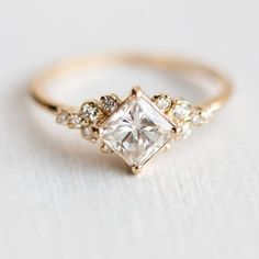 This is a very dainty ring which makes it perfect for stacking. It features a diamond-cut center crystal sprinkled with 12 tiny clear CZ crystals for lots of sparkle to enjoy. Use this as an alternative wedding ring or just as your everyday wear. DETAILS & SIZE Composition: 14K gold plated over copper, CZ stones Measurements: center stone: 5mm, accent stones: 2-3mm, ring band: 18g Read about how to care for our jewelry here. Shop Rings for more options! RETURNS & SHIPPING 60 Day Money Back… Alternative Engagement Rings, Shop Engagement Rings, Engagement Ring Settings, Vintage Engagement Rings, Solitaire Engagement, Solitaire Ring, Wedding Engagement, Nature Engagement Rings, Organic Engagement Rings