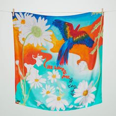 'He loves me' luxurious silk scarf is inspired by 70's psychedelic and folk artwork. Features a lady sitting amongst a colourful scene of blue, orange and turquoise colours, picking daisy petals, wishing her fate of love.     Crafted in Italy from sumptuous silk twill, this silk scarf is the essential accessory for stylish winter layering. Measuring 90 x 90cms, finished with a pin rolled hem. Made in Italy.    Wear yours draped across the chest or tied into a stylish bow against the neck…