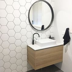 Hex tiled wall, wooden vanity with white top, white square basin, matte black tap and mixer, matte black framed round mirror. Project by - @js_kitchens #taps #interiordesign #bathroom #australia #architecture #bathroomdesign #bathroomcollective Visit our website for more www.bathroomcollective.com.au