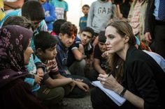 FILE - This June 18, 2013 photo released by the United Nations High Commissioner for Refugees (UNHCR) shows special envoy Angelina Jolie taking notes as she speaks with Syrian refugees in a Jordanian military camp based near the Syria-Jordan border. The Board of Governors of the Academy of Motion Picture Arts and Sciences will present Honorary Awards to Angela Lansbury, Steve Martin and Piero Tosi, and the Jean Hersholt Humanitarian Award to Jolie. All four awards will be pre