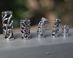 Mountain Dreads www.facebook.com/mountaindreads Mix of 6 Tibetan Silver Dreadlock Hair Beads all with an 8mm Hole Bead 1 - 31mm x 11mm Bead 2 - 30mm x 11mm Bead 3 - 21.5mm x 11mm You will be sent 2 of each, for a total of 6 beads. BRAND NEW CHeck out my other dreadlock beads and accessories, only pay one postage cost no matter how many items purchased at one time. Thanks for looking