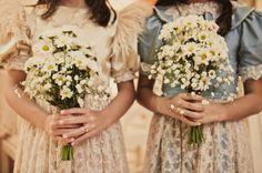 Daminhas carregando flores do campo.