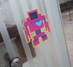A pink and purple sticker lovebot on a glass wall Purple, Pink, Robot, Stickers, Glass, Wall, Drinkware, Corning Glass, Walls