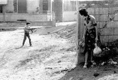 A woman looks at a child soldier in west beirut, 1976