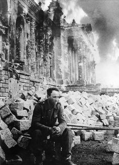 A defeated German soldier sits in front of a burning Reichstag, which had been taken over by Russian troops after a fierce room-to-room battle, Berlin, May 1945 - Imgur