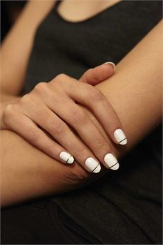 white classic oval shape nail with a thin gold stripe at the tip