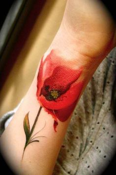 Red poppy flower tattoo on arm, this has to be thee most beautiful tattoo I have ever seen. It's like the tips of the flower petals have bled itself into the skin.