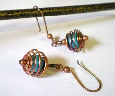 Earrings feature turquoise blue beads (I believe them to be dyed howlite) that have been caged in oxidized copper wire. When the copper wire was