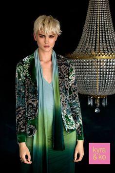 Kyra & Ko, Mooie Kyra & Ko jurk met kleurovergangen van donkergroen naar licht groen en van licht groen naar blauw. De jurk heeft een goede pasvorm en sluit perfect aan op het lichaam. Aan de linkerzijkant van de jurk zit een klein draperie-effect. De jurk heeft een lage hals, welke deels wordt opgevuld met een korte ingezette top. De jurk valt op de knie.