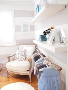 Sweet baby boy's nursery with white and gray horizontal striped walls framing rustic branch clothes rod under stacked white floating shelves.