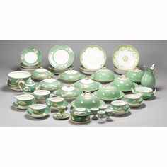 A Derby green-ground part breakfast service 19th century  decorated with vignettes of flowers and picked out in gilding, including four tea cups and saucers, two chocolate cups and saucers, six dessert plates, three muffin dishes with associated covers, four egg cups, one sugar box with missing cover and other items, together with four muffin dishes and a water jug of a similar pattern  Note Large Breakfast Cups