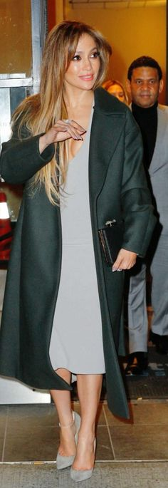 Who made  Jennifer Lopez's jewelry, black clutch handbag, tan suede pumps, and gray ruffle dress?