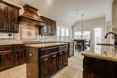 Rich wood kitchen open to the breakfast area // Granite countertops, island, window cutouts in the backsplash