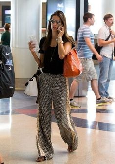 Alessandra Ambrosio wearing Rolex Oyster Perpetual Day-Date Watch, Celine Trapeze Bag, Gerard Darel Simple Bag Cuir Melbourne in Orange and Ella Moss Sun Tile Mix Print Palazzo Pants.