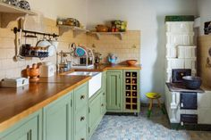 10 The kitchen features grass green cabinets with wooden countertops and a tan tile backsplash - DigsDigs