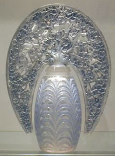 A superb and very rare perfume bottle for Maison Lalique with tiara stopper and deeply moulded base, the floral design heightened with blue staining.