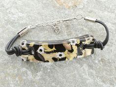 Braccialetto in vetro di Murano originale, con piastra curva.  Il colore nero e le murrine sono appoggiati su una foglia d'oro.  Laccio in caucciù con catena in materiale anallergico (NICKEL FREE).