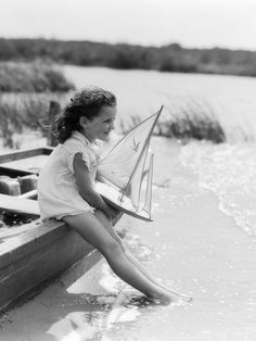 1930s Young Girl at Seashore Holding Sailboat Toy Sitting on Edge of Rowboat Feet in Water Photographic Print at AllPosters.com