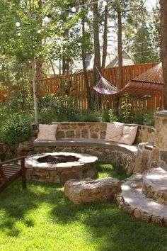Built-in stone fire pit and seating with neutral accent pillows.