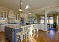An island in gray contrasts with white chairs and cabinets. One of seven newly built homes in the Windsor community from John Wieland Homes in Atlanta, GA.