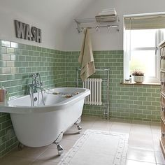 celadon green subway tiles add color to an all white bathroom