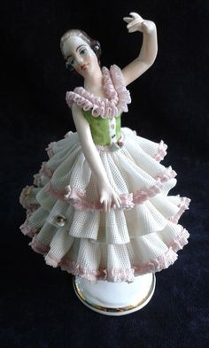 This is the third piece. A striking pose with a green bodice and white and pink lace dress. All three of these carry the Dresden mark on the bottom side.
