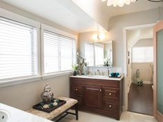 This single vanity bathroom includes a soft beige bench with candles and a decorative silver urn. Organic elements, such as the driftwood seen on the countertop, provide a pure, natural vibe throughout the space.